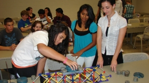 Students (from left) Melissa Garcia of Vineland High School, Nadia Albino of Bridgeton High School and Rosa Melillo of Vineland High School work on a model bridge.